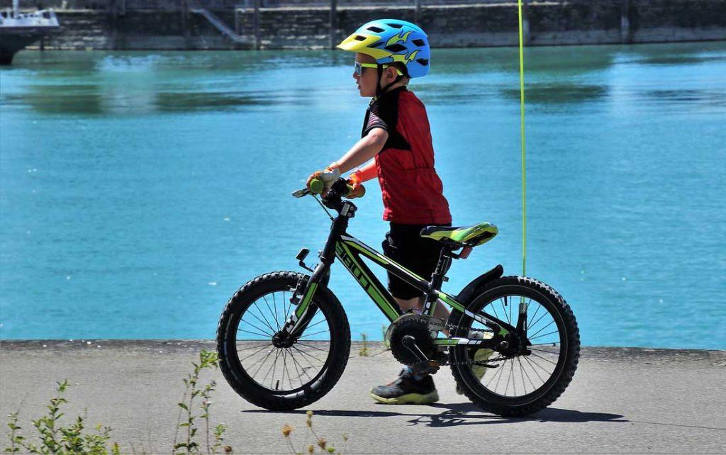un garçon qui marche a coté d'un vélo 18 pouces