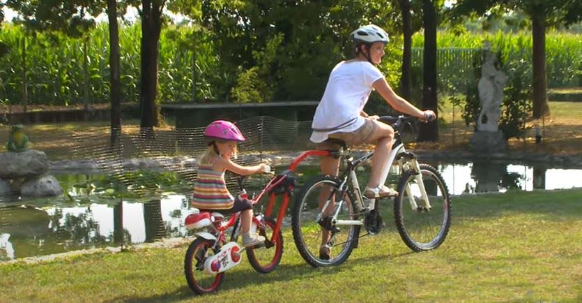 Une maman à vélo qui tire sa fille à vélo à l'aide d'une barre de remorquage